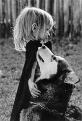 Black-and-white photo of me as a three- or four-year-old child. Oh, and I was blonde back then.'m standing next to a dog, Lightning, who is looking up at me. She's a Malamute who's almost as tall as I am. Oh, and I'm wearing a cape, like the little bad ass I was when I was that young.